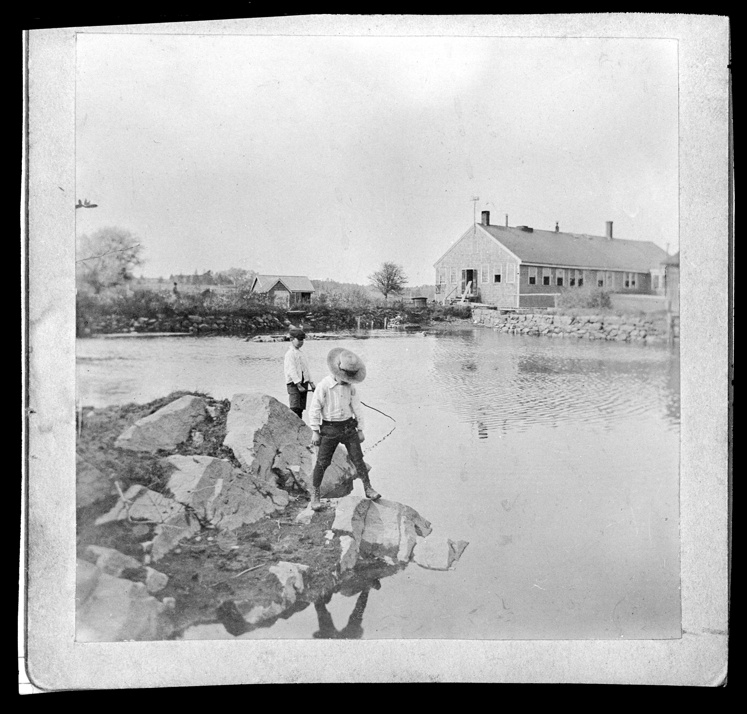 Two boys fishing in the millpond of C. Drew & Co., no date