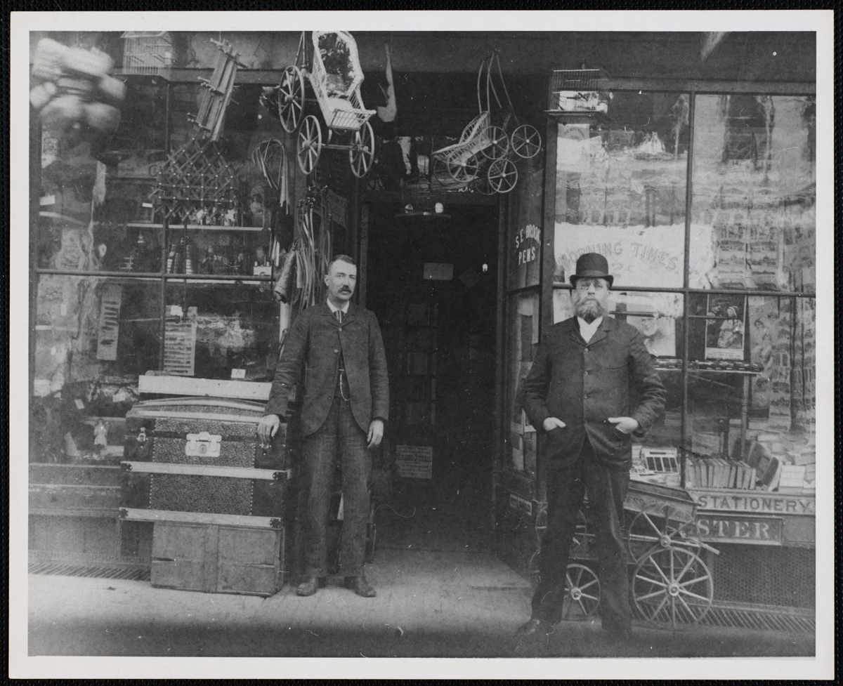 Two men at the entrance of the store at 58-60 Summer Street, circa 1875